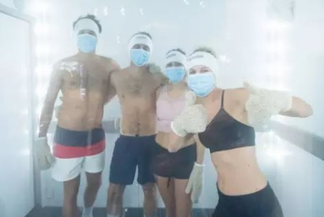 Four people standing in a cryotherapy chamber after COVID-19